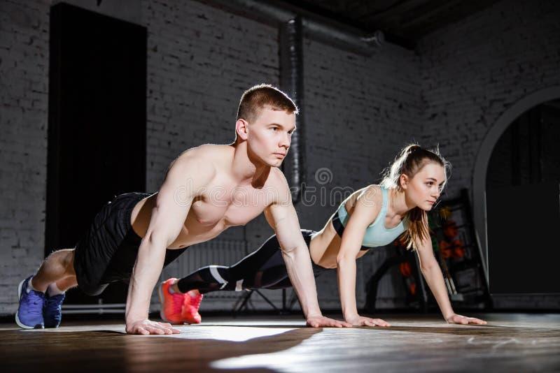 健身、体育、训练、健身房和生活方式概念-做在健身房的年轻夫妇俯卧撑 库存图片