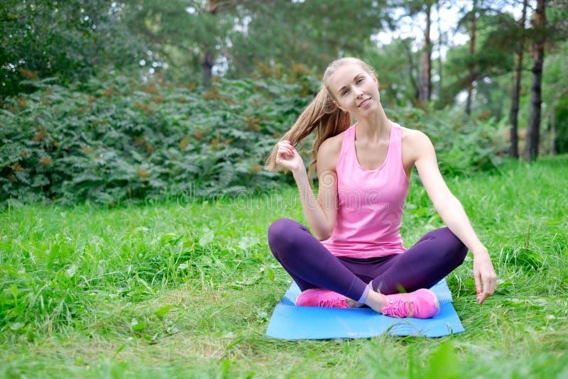 健身、体育、训练、公园和生活方式概念-做在席子的微笑的妇女锻炼户外 免版税库存照片