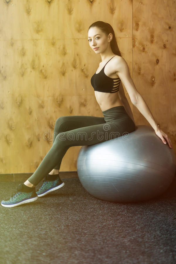 健身、体育、训练、健身房和生活方式概念-做在健身球的少妇锻炼 库存照片