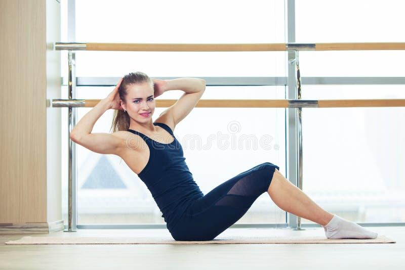 健身、体育、训练和人概念-做在席子的微笑的妇女胃肠锻炼在健身房 免版税图库摄影