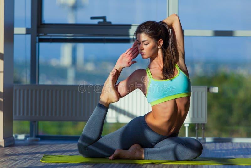 健身、体育、训练和生活方式概念-舒展在健身房的席子的微笑的妇女 从一个大窗口的光 免版税库存图片