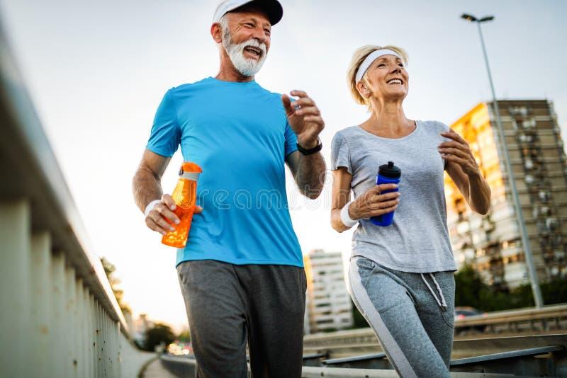 健身、体育,人,行使和生活方式概念-资深夫妇赛跑 免版税库存照片