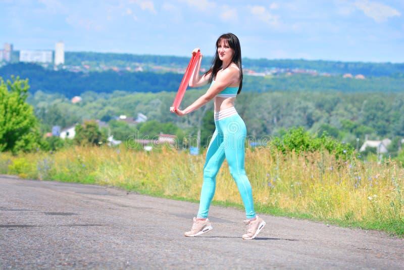健身与橡胶抵抗的女孩训练 库存图片