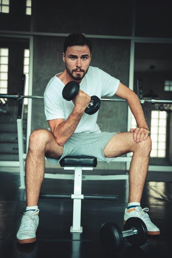 健身人行使举在健身房的哑铃 做举重和锻炼健康的白种人帅哥画象 免版税库存照片