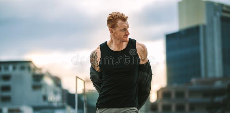 健身人身分的画象在去除他的衬衣的屋顶的 库存图片