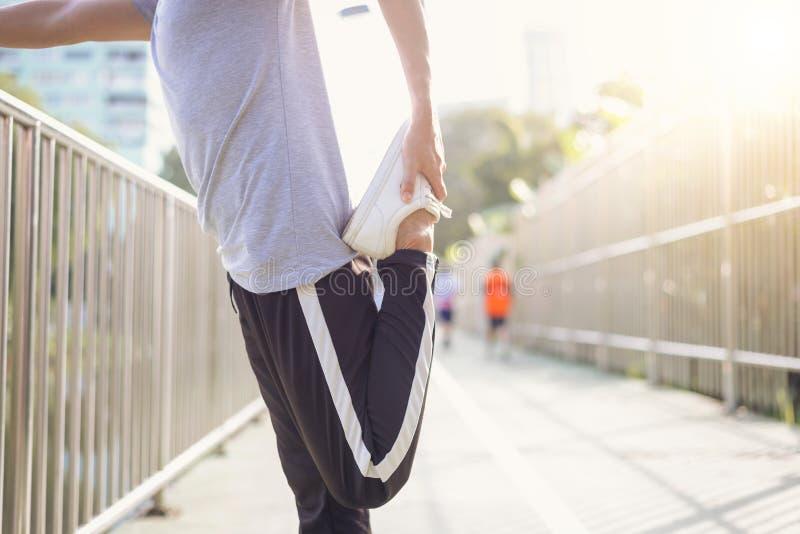 健身体育人塑造做瑜伽在街道的运动服健身锻炼 做训练锻炼的适合的年轻亚裔人在早晨 免版税图库摄影