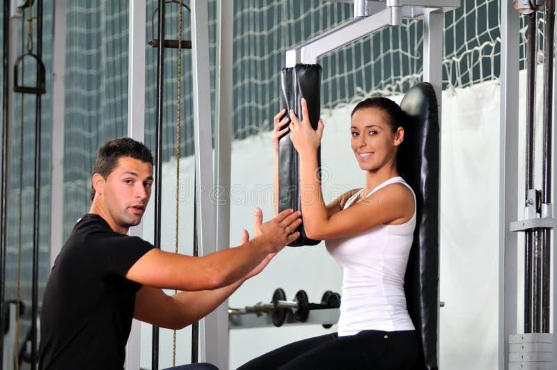 健身俱乐部的妇女与培训人 免版税库存图片