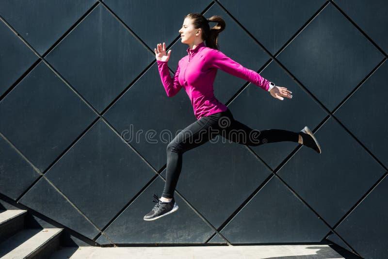 健身做瑜伽在街道的时尚运动服的体育女孩健身锻炼,户外运动,都市样式 免版税库存图片