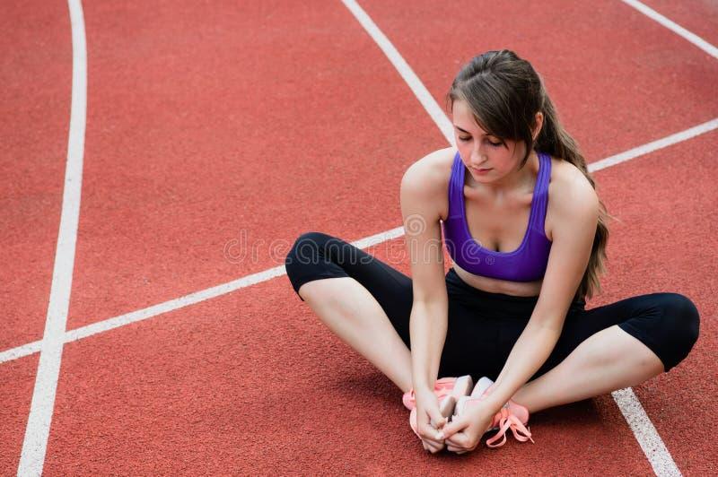 健身做瑜伽在街道的时尚运动服的体育女孩健身锻炼,户外运动,都市样式 免版税库存照片