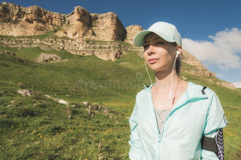 健身听到在自然的音乐的赛跑者妇女 美丽的女孩佩带的耳机earbuds和赛跑画象  库存图片