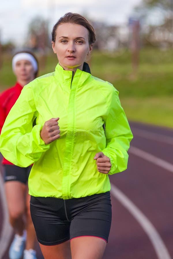 健身和健康生活方式概念 有两个的女运动员在体育场的跑的锻炼 图库摄影