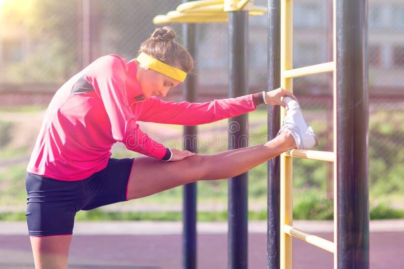 健身和健康生活方式概念 有被集中的白种人的女运动员舒展锻炼的腿肌肉 库存照片