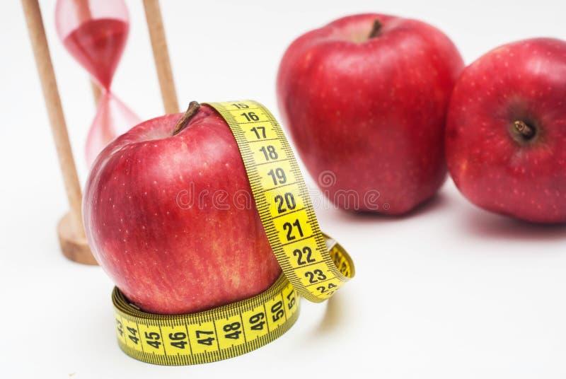 健身和健康食物 关闭与测量Metter的红色苹果计算机并且铺沙在背景的玻璃时钟 查出在白色 库存图片