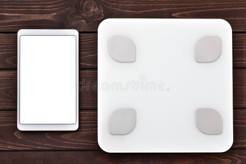 健身和减肥概念、白色标度和片剂在木桌,顶视图上 免版税库存图片