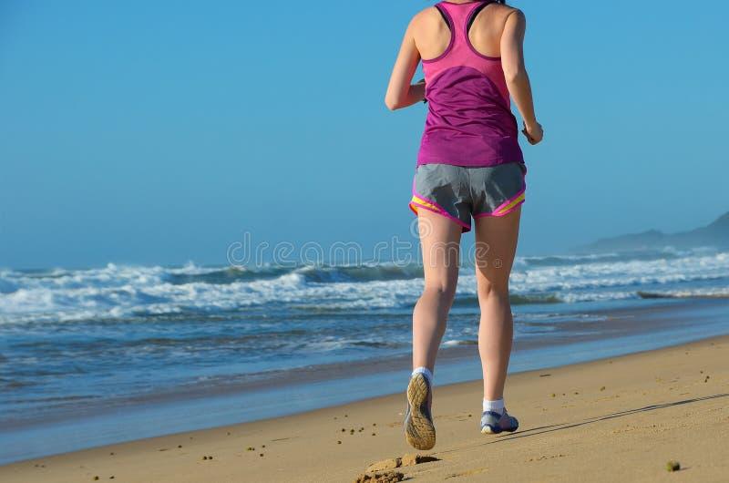 健身和赛跑在海滩、妇女赛跑者解决在沙子的在海附近,健康生活方式和体育 免版税库存图片