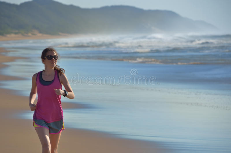 健身和赛跑在海滩、愉快的妇女赛跑者跑步在沙子的在海附近,健康生活方式和体育 库存照片