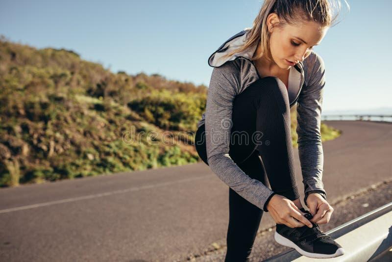 健身在栓她的鞋带的路旁的妇女身分 拉紧她的在旁边栏杆的健身穿戴的妇女鞋带  库存照片