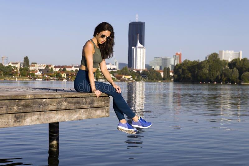 健身女孩佩带的绑腿、运动鞋和太阳镜 库存图片