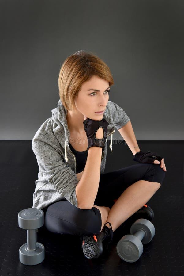 健身女孩坐realxing的地板 库存照片