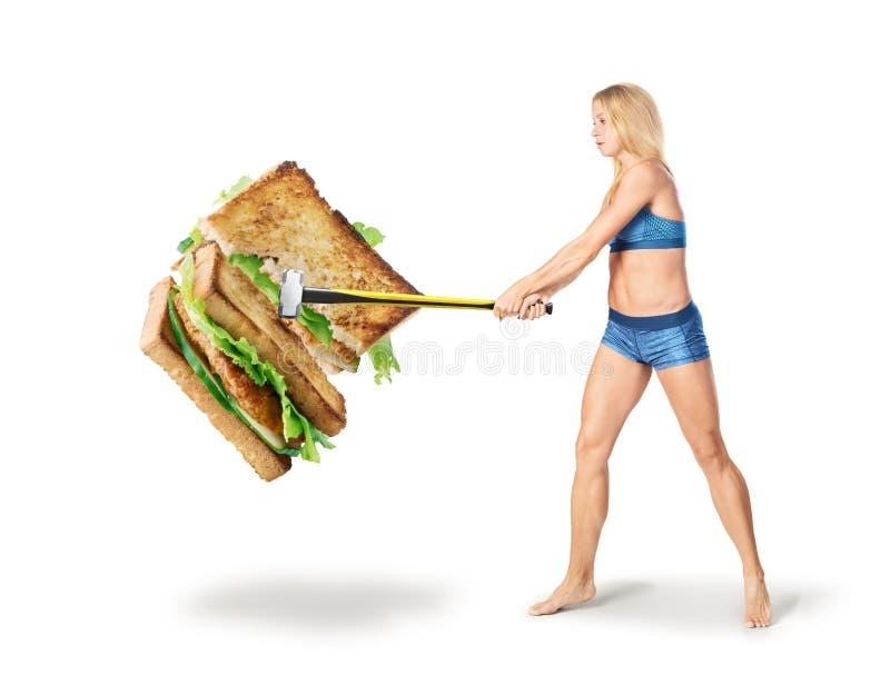 健身女孩打破与一把锤子的一个三明治在白色背景 库存图片