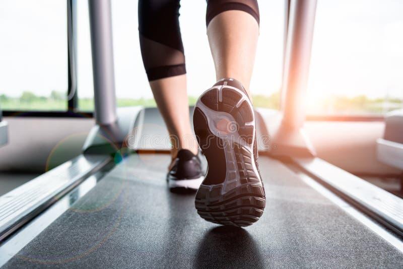 健身女孩跑在踏车的,有肌肉腿的妇女在g 免版税库存照片