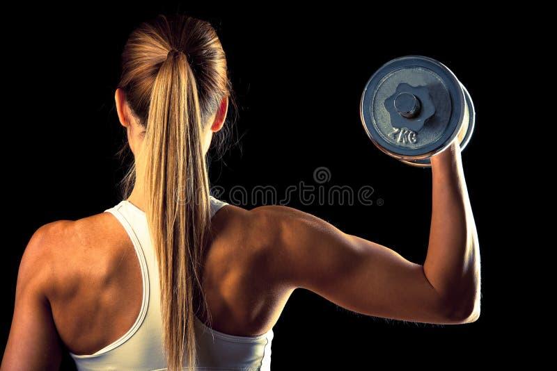健身女孩-解决与哑铃的可爱的少妇 免版税库存图片
