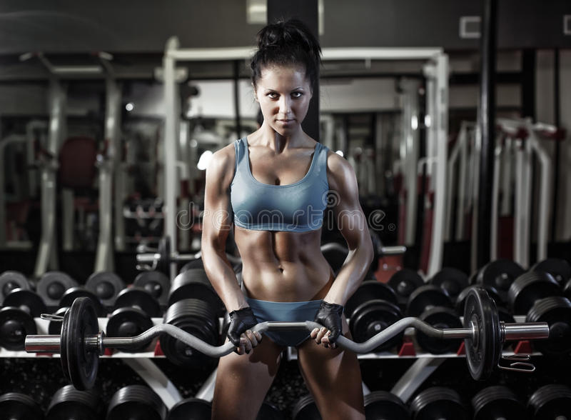 健身妇女与哑铃的俯卧撑二头肌 免版税图库摄影