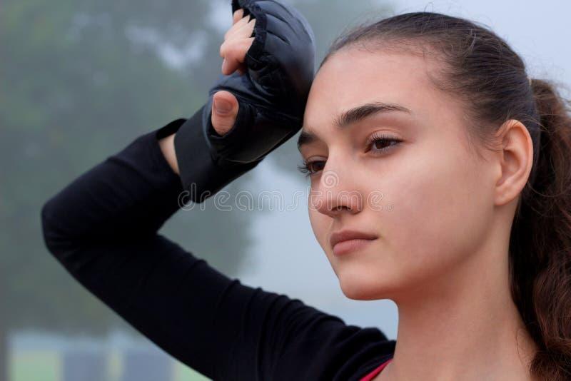 年轻健身妇女休息在拳击室外训练的锻炼期间 免版税库存照片