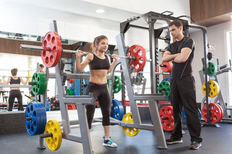 健身妇女和个人教练员在健身房 库存照片