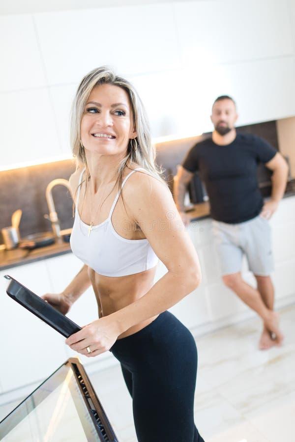 健身妇女在厨房里,人在背景中 一起烹调丈夫妻子 库存照片