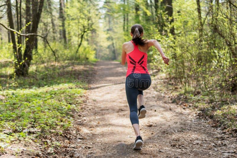 健身妇女奔跑在春天晴朗的森林里 免版税库存照片