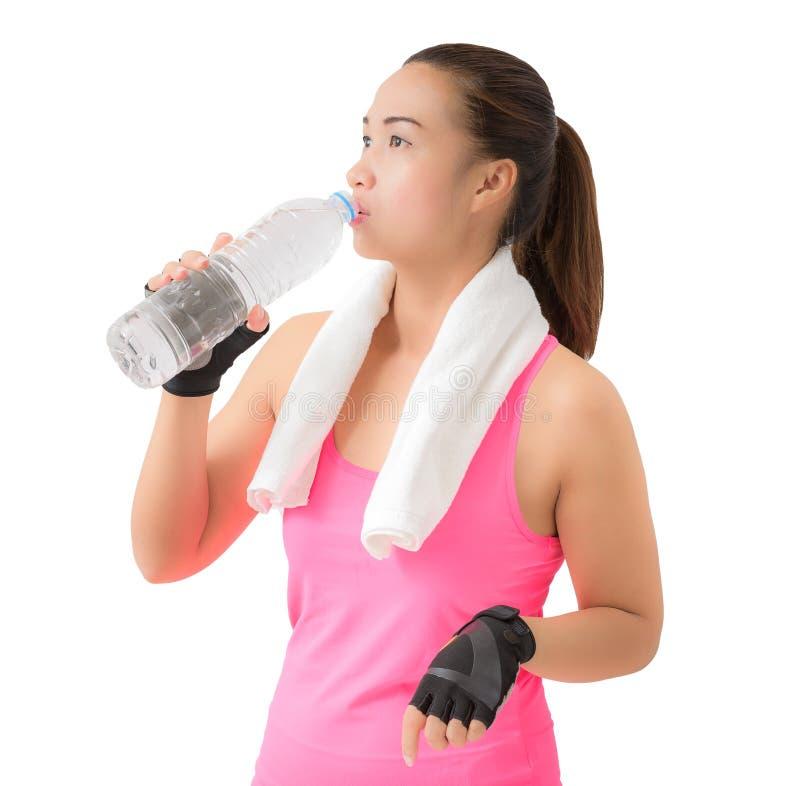 健身妇女愉快的微笑的举行的水瓶瓶和drin 免版税库存图片