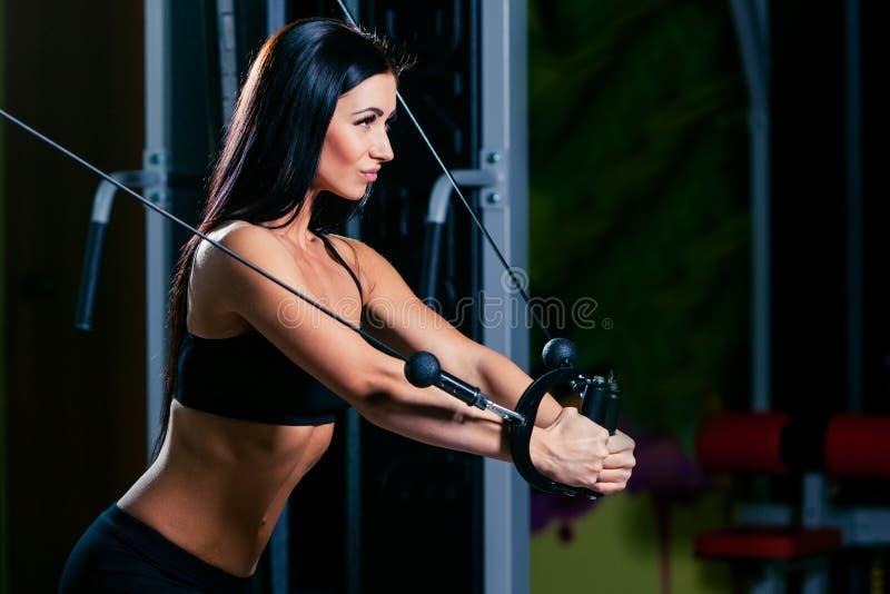 年轻健身妇女执行与锻炼机器缆绳天桥的锻炼在健身房,水平的照片 免版税库存图片