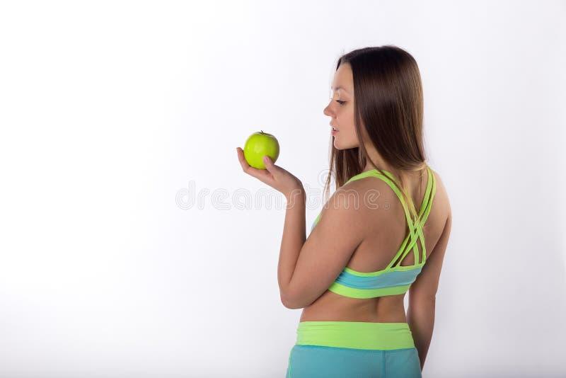 健身妇女用在手中苹果,后面看法 免版税图库摄影