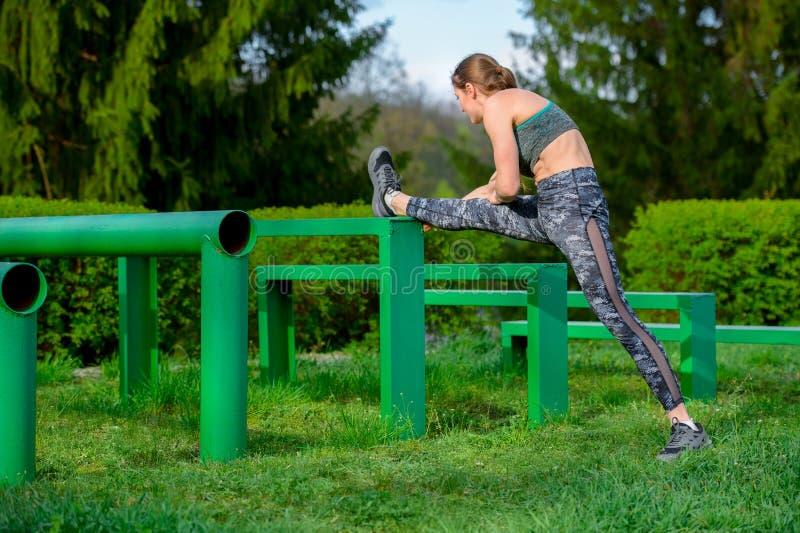 健身妇女舒展腿,在室外连续锻炼的锻炼前做准备 运动员舒展腿筋肌肉 免版税库存图片