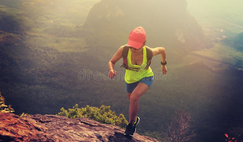 健身妇女运行由山上面决定的足迹赛跑者 免版税图库摄影