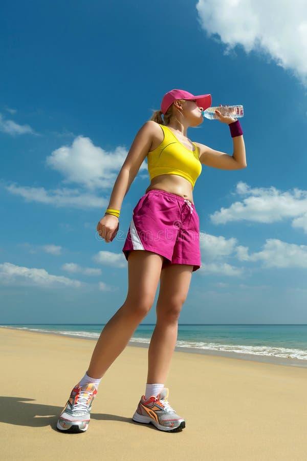 健身妇女饮用水在跑在海滩以后。 库存图片