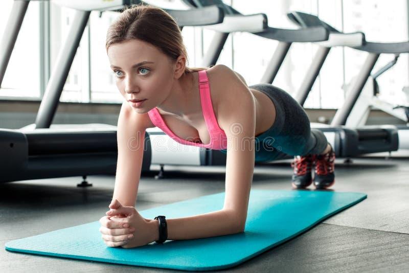 健身房健康生活方式身分的少女在席子被集中的特写镜头的板条姿势 库存照片
