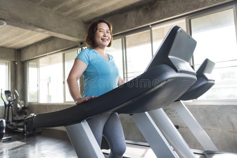 健身房健身的愉快资深妇女的赛跑者微笑和 年长健康生活方式 图库摄影