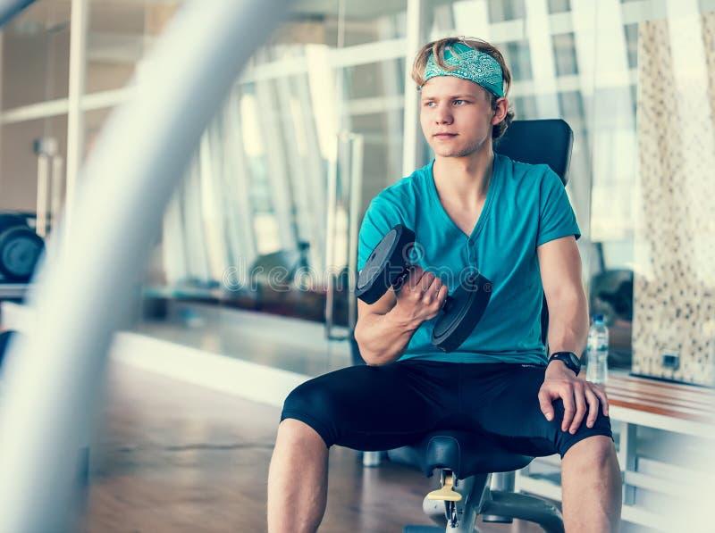 健身房大厅训练的年轻人与哑铃 免版税库存照片