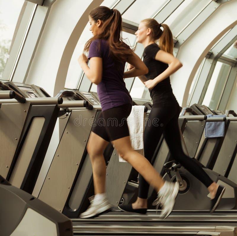 健身房射击了-跑在机器,踏车的少妇 免版税库存照片