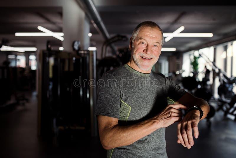 健身房测量的时间的一名快乐的老人,当做锻炼时 复制空间 免版税库存图片