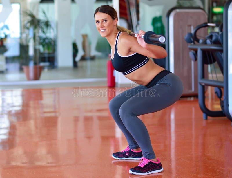 健身房男人和妇女俯卧撑与哑铃的力量pushup在锻炼 免版税库存图片