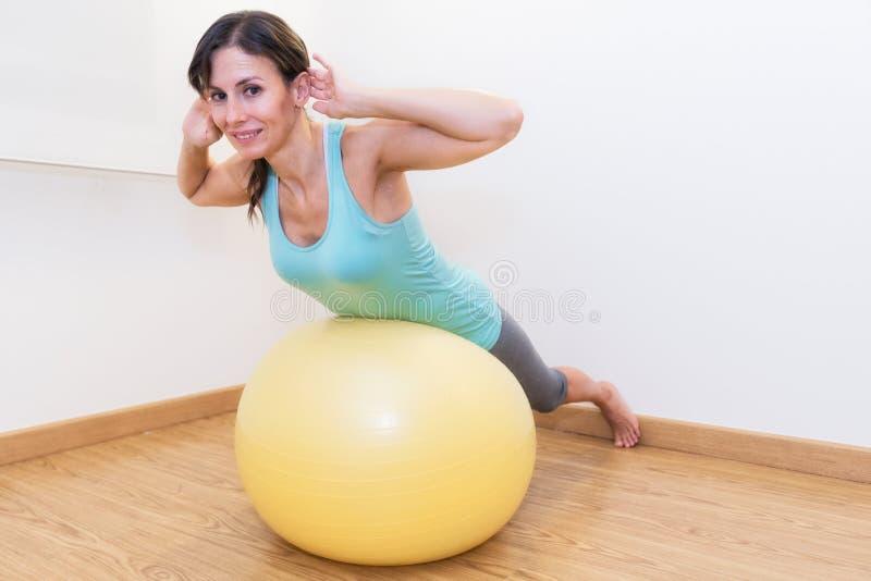 健身房的健身妇女在pilates球 做在健身球的少妇锻炼 免版税库存照片