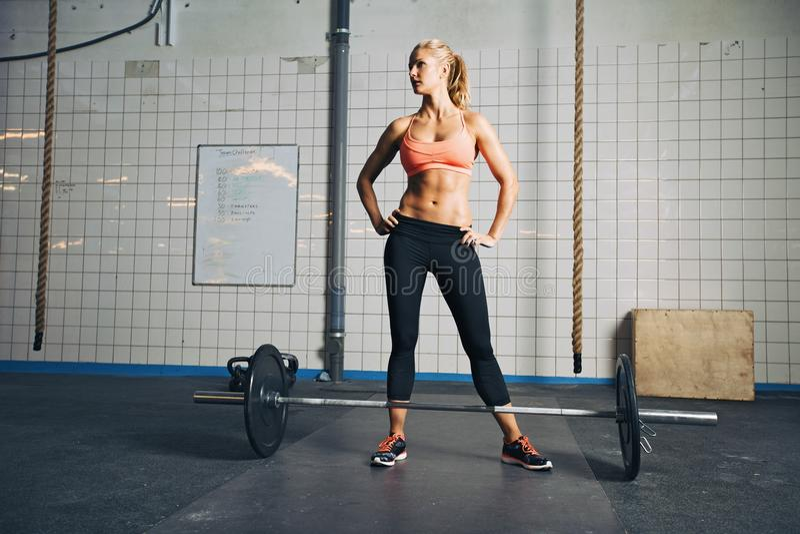 健身房的坚强的crossfit女性与杠铃 库存照片