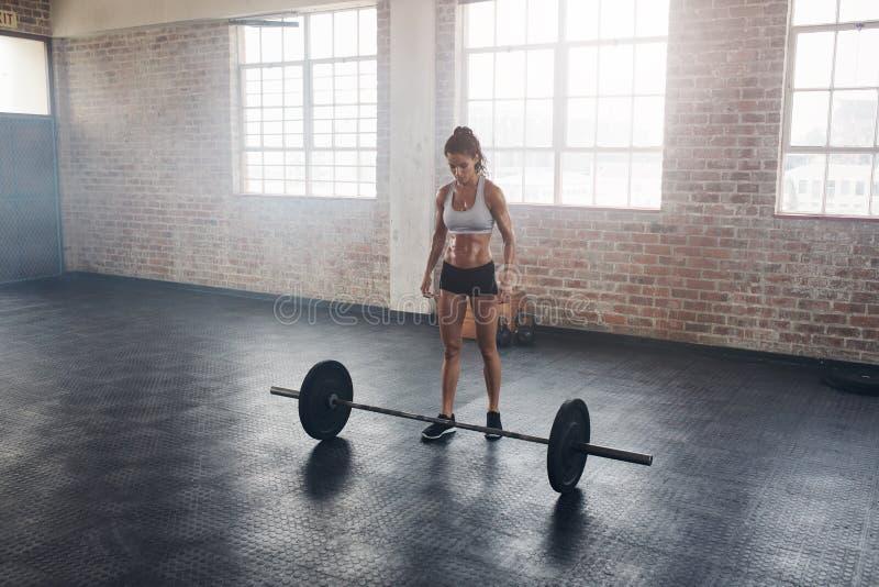健身房的坚强的crossfit女性与杠铃 免版税库存图片
