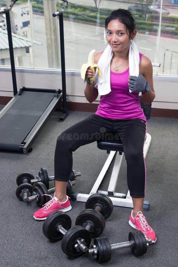 健身房的妇女吃香蕉的 库存照片