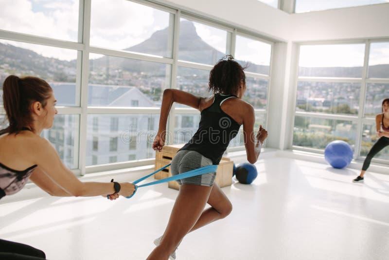 健身房的妇女在抵抗带锻炼期间 免版税库存图片