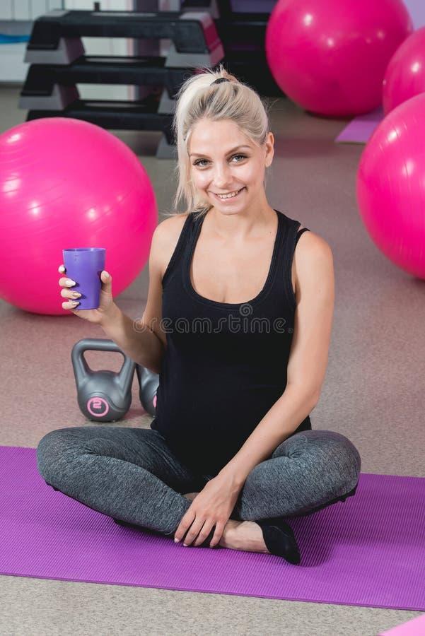 健身房的孕妇坐放松在训练以后的席子保留适合  免版税库存照片