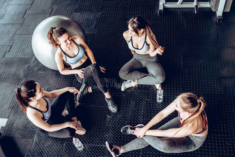 健身房的年轻人坐地板,谈话 免版税库存照片